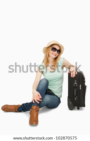 Blonde-haired woman sitting near a suitcase against white background - stock photo
