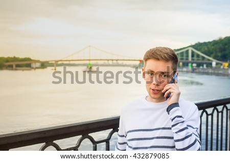 Blonde haired young man at striped shirt using his phone near the river