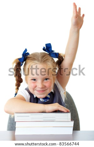 Blonde happy schoolgirl in blue dress and matching tie rises her hand up, while sitting at school desk with pile of books, isolated on white - stock photo