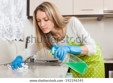 Blonde housewife cleaning furniture in kitchen with detergent - stock photo