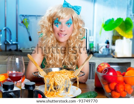 Blonde hungry girl funny on kitchen with pasta and fashion blue makeup - stock photo