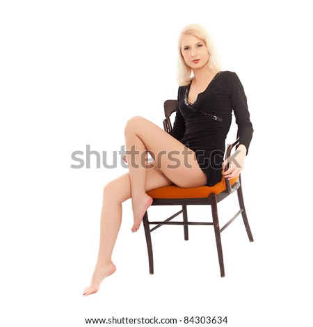 blonde in a black dress sitting on an ancient chair. isolated on white - stock photo