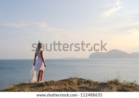 Blonde in a white dress standing on the mountain and looks at the sea - stock photo