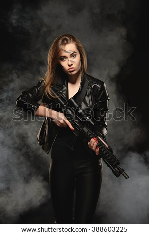 Blonde in black taking aim with a rifle. Photographed in studio on a black background with smoke