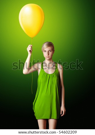 blonde in green dress with the yellow balloon - stock photo