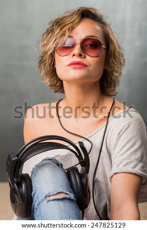 Blonde in headphones. Stylish girl in casual clothes on a gray background. Blonde posing in the studio. - stock photo