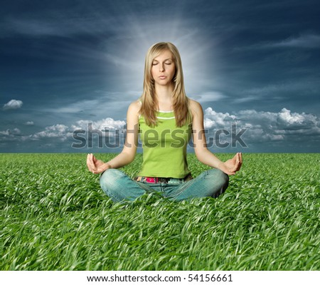 Blonde in lotus pose in green grass on blue summer sky - stock photo