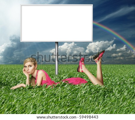 Blonde in pink dress with billboard in green grass on blue summer sky - stock photo