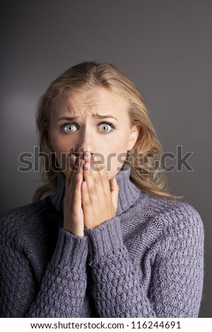 Blonde in shock. Photos in the studio. Girl in a sweater - stock photo