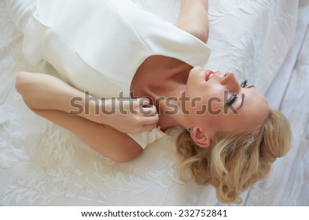 blonde in white dress lying on the bed