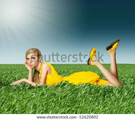 Blonde in yellow dress in green grass on blue summer sky - stock photo