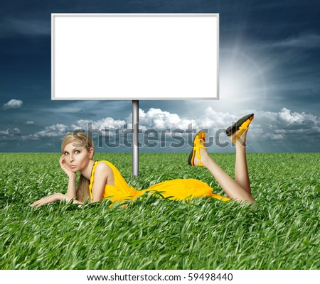 Blonde in yellow dress with billboard in green grass on blue summer sky - stock photo