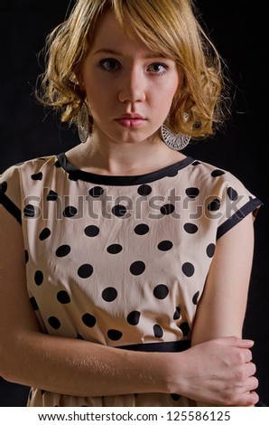 Blonde innocent Caucasian young woman wearing a vintage dress with dots pattern - stock photo