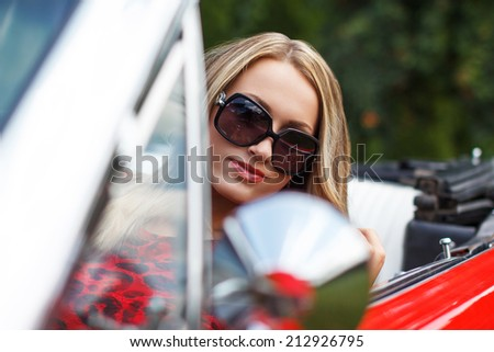 Blonde lady in red cabriolet, outdoor portrait - stock photo