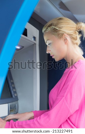Blonde lady using an automated teller machine . Woman withdrawing money or checking account balance. - stock photo