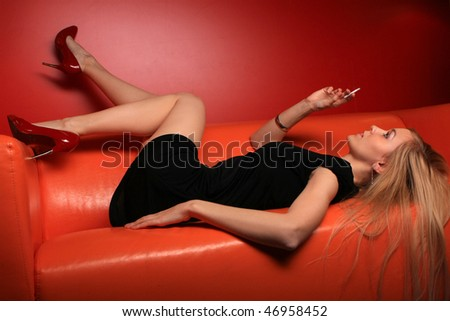 blonde lies on a orange sofa and holds a cigarette in a hand - stock photo