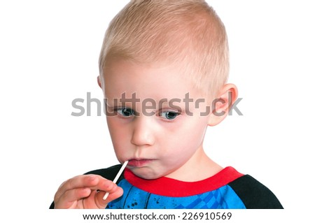 Blonde little boy with big blue eyes eating a candy sucker. Isolated on a white background