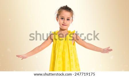 Blonde little girl dancing over ocher background - stock photo