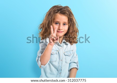 Blonde little girl doing victory gesture - stock photo