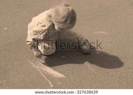 blonde little girl on the pavement with a chalk, sepia toned - stock photo