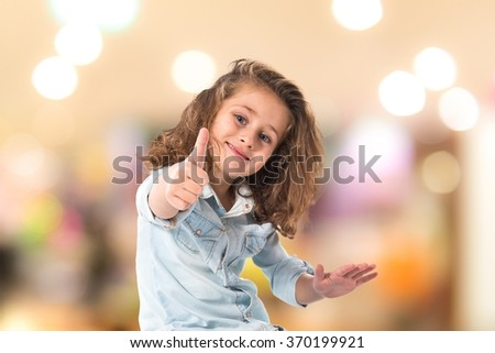 Blonde little girl with thumb up on unfocused background - stock photo