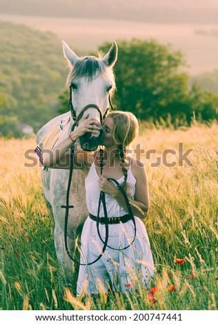blonde long hair woman kissing beautiful horse - stock photo