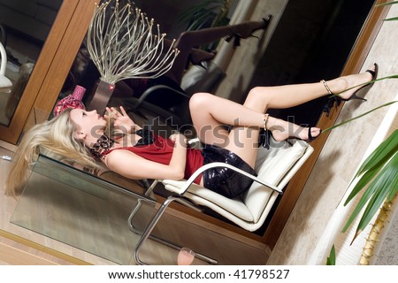 Blonde lying on the glass table crossing one leg over the other - stock photo
