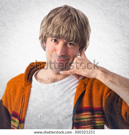 Blonde man making phone gesture over grey background - stock photo