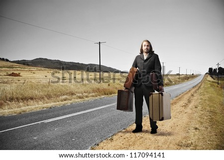 Blonde man, on a long road of countryside, holding many suitcases - stock photo
