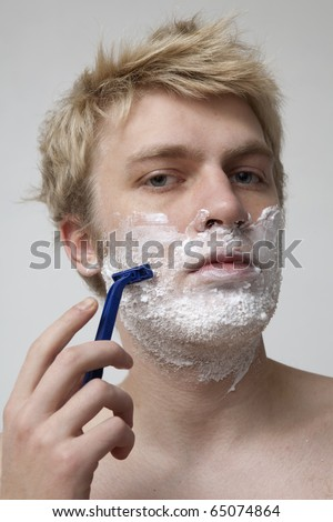 Blonde man shaving face in bathroom, portrait