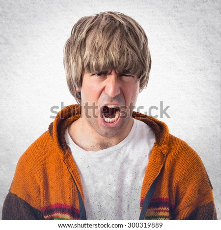 Blonde man shouting over grey background