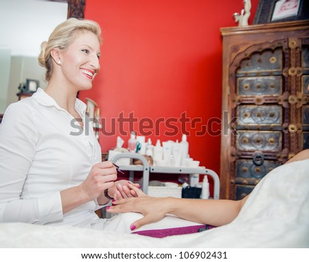 Blonde manicurist have fun with her client - stock photo