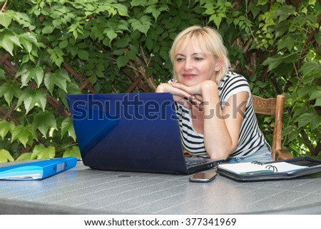 Blonde middle aged woman is sitting outdoors on the terrace  with open notebook, diary and smart phone on the table. She is supporting her chin with both hands and looking into the laptop.