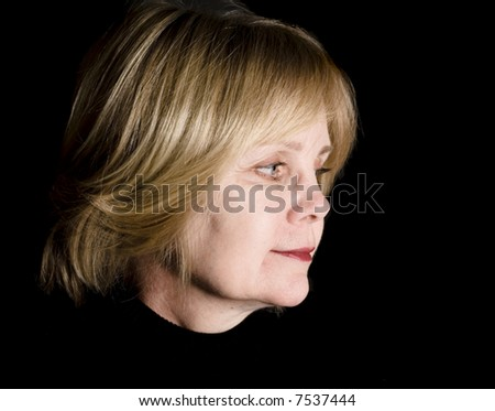 Blonde middle-aged woman looking back on the past