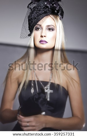 Blonde model in a strapless top, cross jewellery and a hat with veil posing in a studio