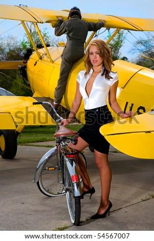 Blonde model standing near a WWI biplane - stock photo