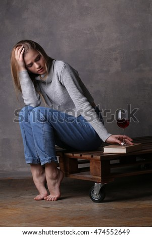 Blonde model touching a book. Gray background
