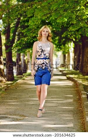 blonde model walking in park - stock photo