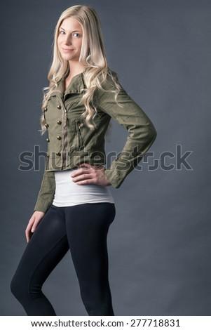Blonde model wearing jacket, tank top and leggings.   - stock photo