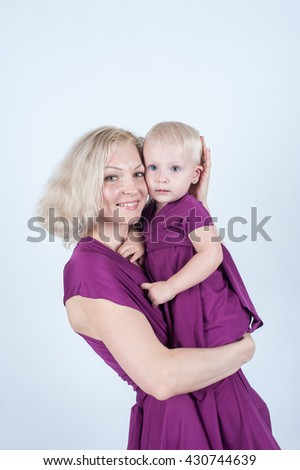 Blonde mom holding a little girl, they are the same dress in the Studio