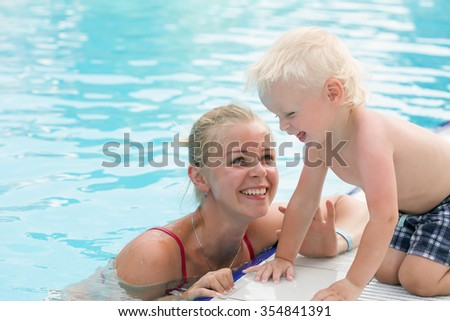 Blonde mother and her little son have fun by a swimming pool - stock photo