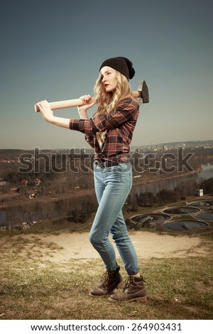 Blonde nice young woman holding a giant hammer - stock photo
