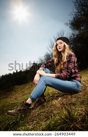 Blonde nice young woman sitting above city on hill