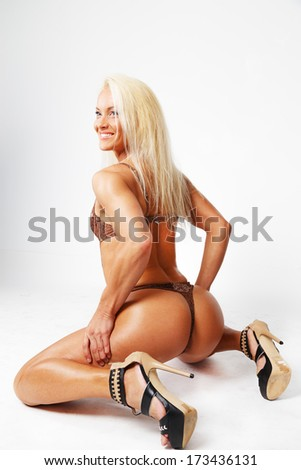Blonde on high heels sits and smiles - stock photo