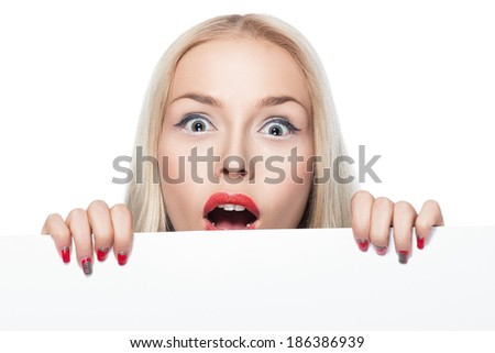 Blonde peeking out from behind a poster on which you can make advertising inscription or image. - stock photo