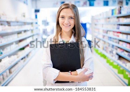 Blonde pharmacist with clipboard and prescription drugs - stock photo