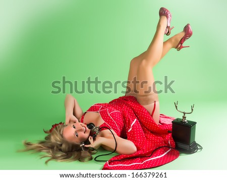 Blonde pin-up girl talking on a vintage telephone - stock photo