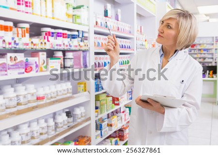 Blonde pointing medicine with her pen in the pharmacy - stock photo