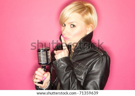 blonde pop star on pink background singing , holding retro mic