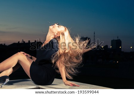 Blonde posing sexually outdoors with her long hairs